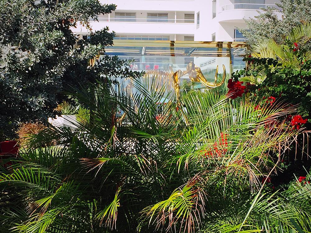 Well hidden, behind tropical plants stands the golden mammoth.